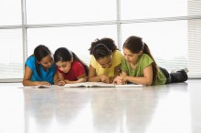 Preteen girls of mutiple ethnicities lying together on floor with schoolwork.